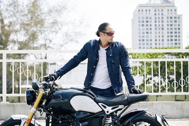 오토바이에 서서 멀리 바라보는 데민 재킷을 입은 자신감 있는 청년