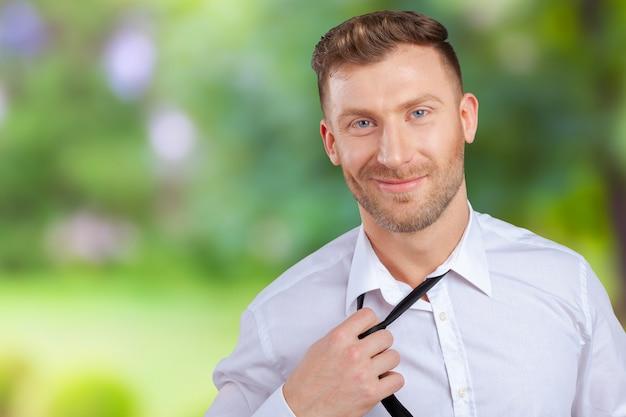 Уверенный молодой человек в рубашке и галстуке поправляя галстук