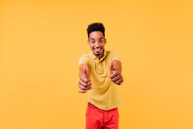 Уверенный молодой человек смотрит вправо и показывает палец вверх. фотография восторженного стильного парня в помещении.