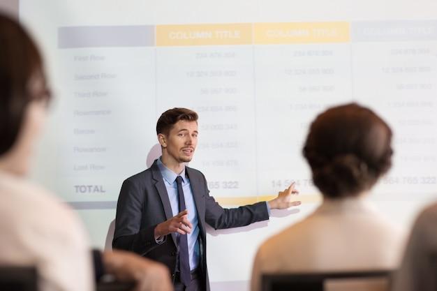 Уверенный молодой человек делает презентацию в команда
