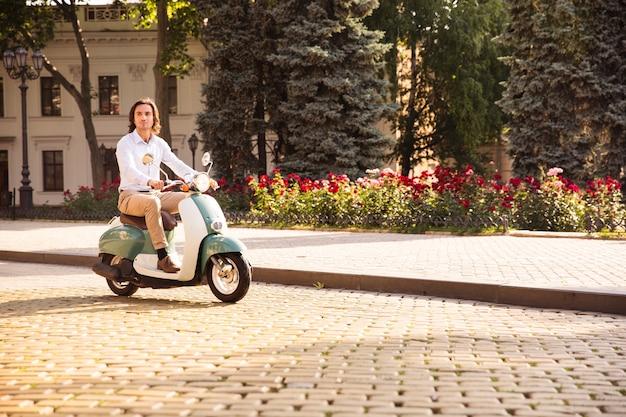 朝の街の通りをスクーターに乗って自信を持って若い男