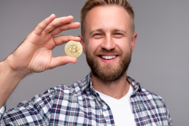Confident young man showing bitcoin to camera