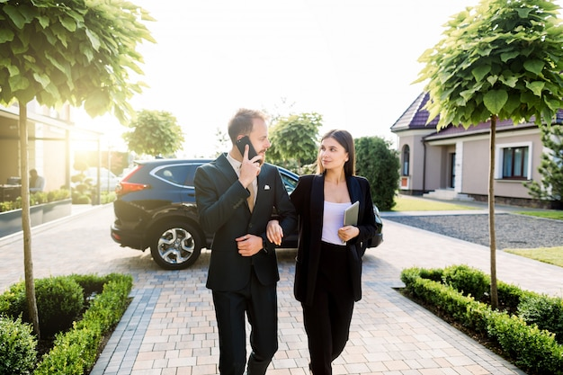 Confident young man talking phone and explaining something to his pretty female colleague while coming for work and business meeting together. business couple walking together outdoors