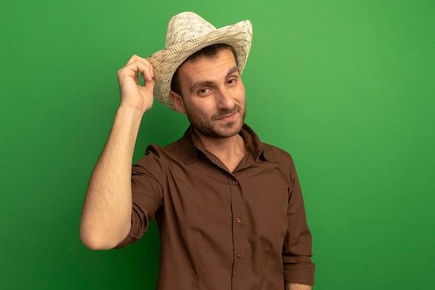 緑の壁に隔離された正面を見てそれをつかんでビーチ帽子をかぶって自信を持って若い男