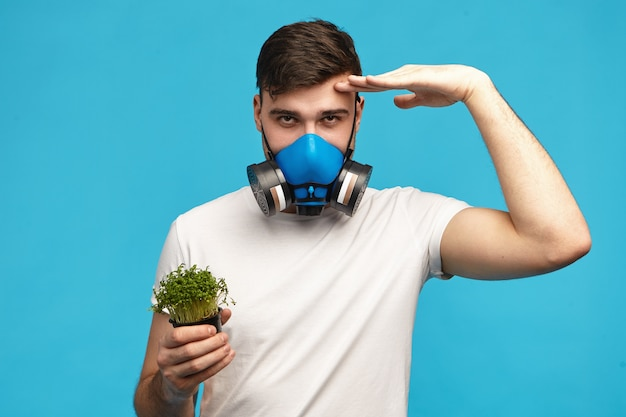 Confident young man wearing gas mask holding hand at his forehead as sign that her ready to protect you from pesticides and genetically modified organisms, holding microgreens