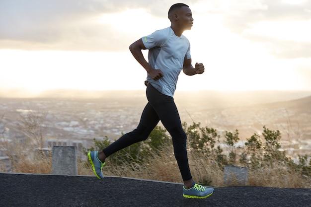 자신감이 넘치는 청년은 흰색 티셔츠, 검은 색 레깅스와 운동화를 입고 고속도로에서 혼자 달리고 심호흡을하며 지구력을 보여주고 아침 시간을 즐깁니다. 사람, 경주, 라이프 스타일 컨셉