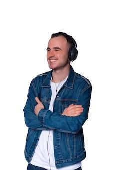 Уверенный в себе молодой человек со скрещенными руками слушает музыку или аудиокнигу в наушниках.