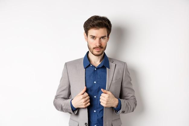 Уверенный в себе молодой человек с костюмом для ремонта бороды и дерзким взглядом в камеру, чувствуя себя готовым и решительным, стоя на белом фоне.