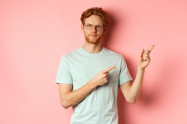 生姜の髪とあごひげを持った自信のある若い男が喜んで笑顔で右上の指を指しています...