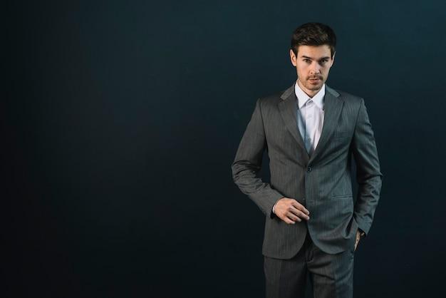 Уверенный молодой человек с рукой в кармане на черном фоне