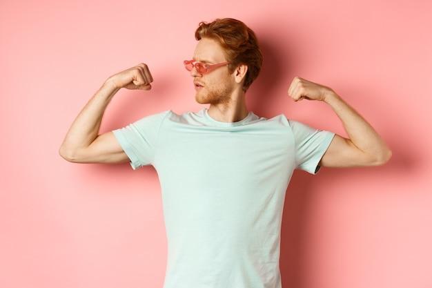 빨간 머리를 가진 자신감이 젊은 남자, 여름 선글라스와 티셔츠를 입고 강하고 맞는 신체 근육, 플렉스 팔뚝을 보여주고 카메라, 분홍색 배경을 시원하게 응시합니다. 운동 및 체육관 개념