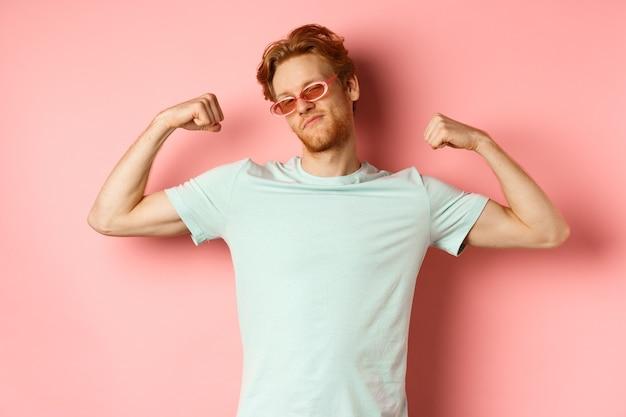 강하고 맞는 몸매를 보여주는 여름 선글라스와 티셔츠를 입은 빨간 머리를 한 자신감 있는 청년