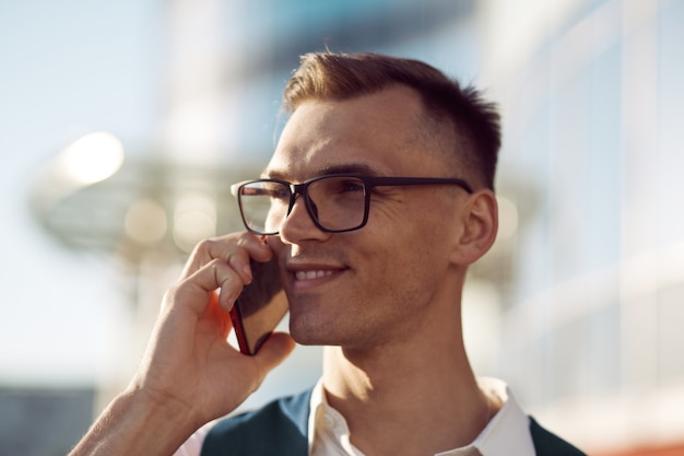 Confident young man with a smartphone on a city background