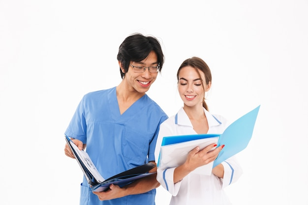 Confident young multiethnic doctors couple wearing unif, analyzing folders