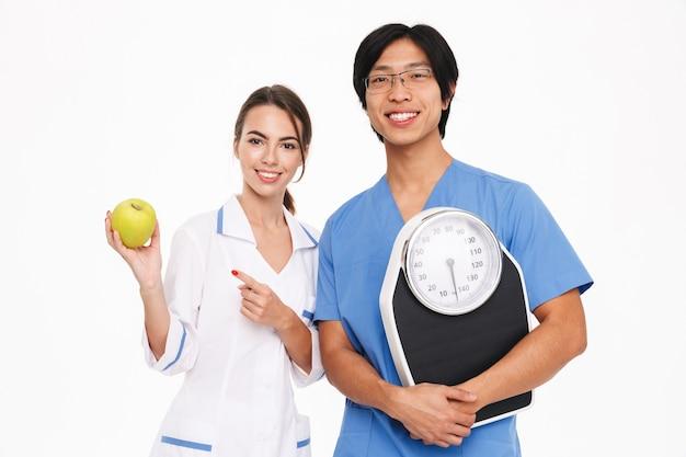 Уверенная молодая многонациональная пара врачей в униформе, стоящая изолированно над белой стеной, показывая зеленое яблоко, держа весы