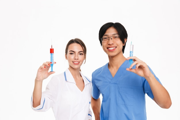 Confident young multiethnic doctors couple wearing uniform standing isolated over white wall, showing syringes