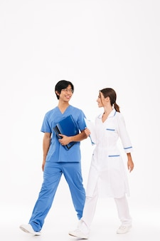Confident young multiethnic doctors couple wearing uniform walking isolated over white wall, carrying folders