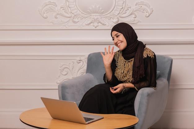 自信を持って若いイスラム教徒の女性が自宅でウェブカメラ会議のビデオ通話を見てください。