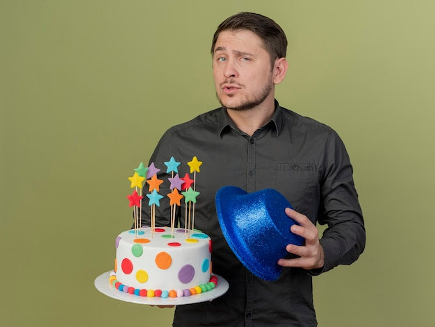 올리브 그린에 고립 된 파란색 모자와 케이크를 들고 검은 셔츠를 입고 자신감 젊은 파티 남자