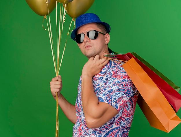 파란색 모자와 안경을 들고 풍선을 들고 녹색에 고립 된 어깨에 선물 가방을 넣어 자신감이 젊은 파티 남자