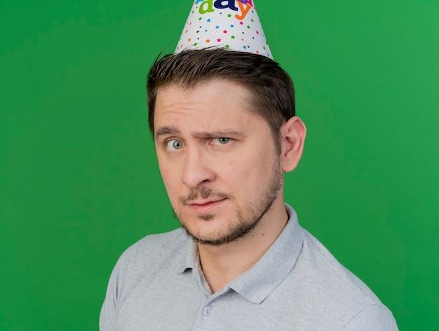 Fiducioso giovane partito ragazzo indossa una camicia grigia e cappello di compleanno isolato sul verde
