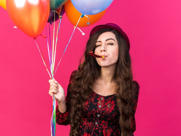 Confident young party woman wearing party hat holding balloons blowing party horn with closed eyes isolated on pink wall