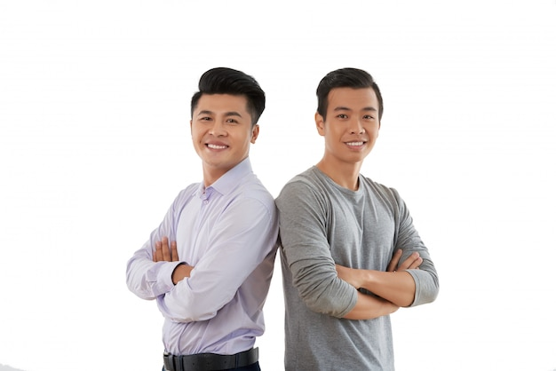 Confident young people standing shouder to shoulder with arms folded against white background