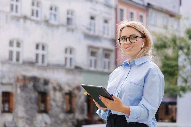 デジタルタブレットを持って、市内中心部に立っている間、先を見据えて眼鏡をかけている自信のある若者。屋外でモダンなgagdetを使用して幸せなブロンド。