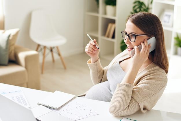 書類を持って机に座って、オフィスで電話でクライアントに答える眼鏡をかけた自信のある若い妊娠中の実業家