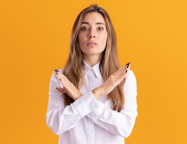Confident young pretty caucasian girl crosses hands gesturing no sign isolated on orange wall with copy space