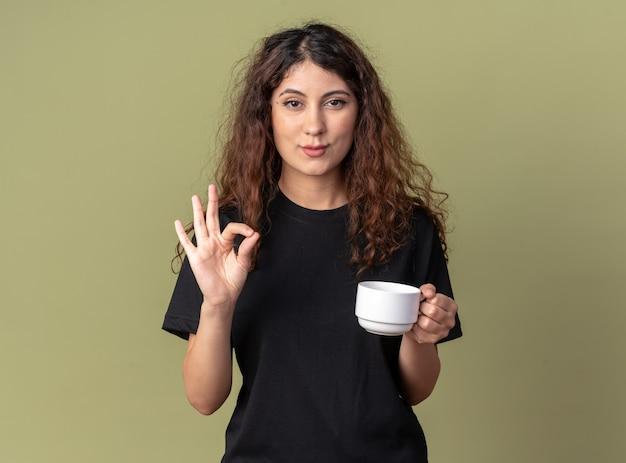 Уверенная молодая симпатичная кавказская девушка держит чашку чая и делает знак ок, изолированную на оливково-зеленой стене с копией пространства