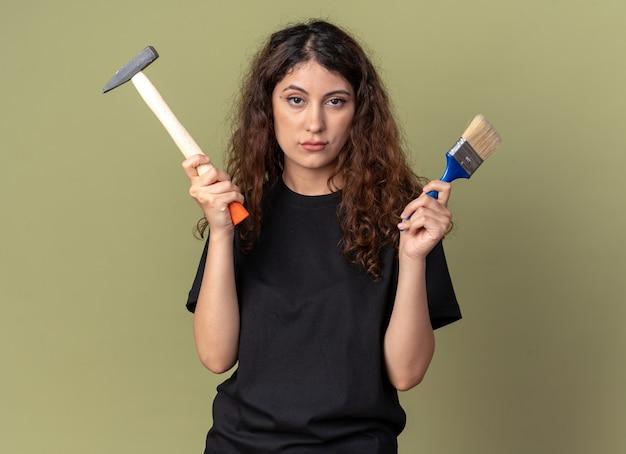 Fiducioso giovane bella ragazza caucasica con pennello e martello isolato su parete verde oliva