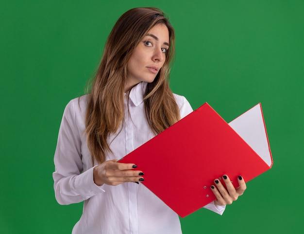 자신감 있는 젊은 백인 소녀는 복사 공간이 있는 녹색 벽에 격리된 파일 폴더를 보유하고 있습니다.