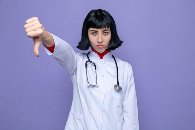 聴診器の親指を下に向けて医者の制服を着た自信を持って若いかなり白人の女の子