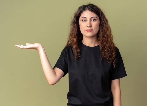Fiducioso giovane bella ragazza caucasica che punta con la mano sul lato isolato sul muro verde oliva