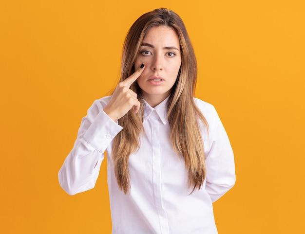 Уверенная молодая симпатичная кавказская девушка кладет палец на веко и смотрит в камеру на оранжевом