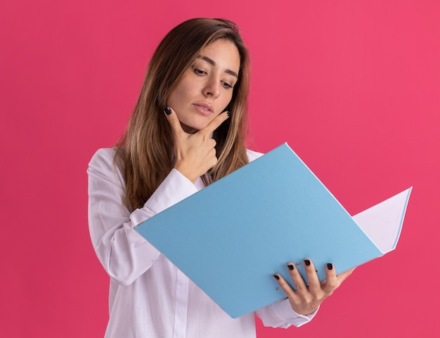 Confident young pretty caucasian girl puts hand on chin holding and looking at file folder