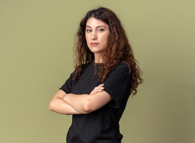 Fiduciosa giovane bella ragazza caucasica in piedi con postura chiusa in vista di profilo isolata su parete verde oliva con spazio di copia