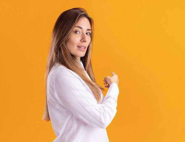 Уверенная молодая симпатичная кавказская девушка стоит боком, указывая на сторону, изолированную на оранжевой стене с копией пространства
