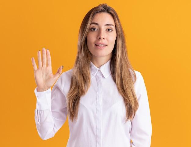 Уверенная молодая симпатичная кавказская девушка стоит с поднятой рукой, изолированной на оранжевой стене с копией пространства