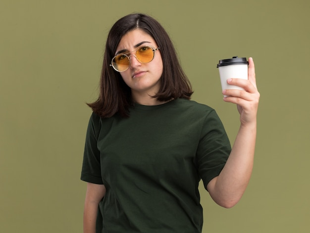 Confident young pretty caucasian girl in sun glasses holding paper cup isolated on olive green wall with copy space