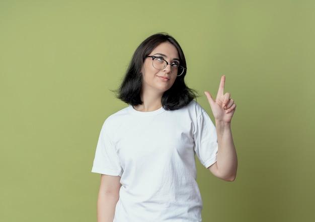 Уверенная молодая симпатичная кавказская девушка в очках смотрит вверх и делает жест неудачника, изолированного на оливково-зеленом фоне с копией пространства