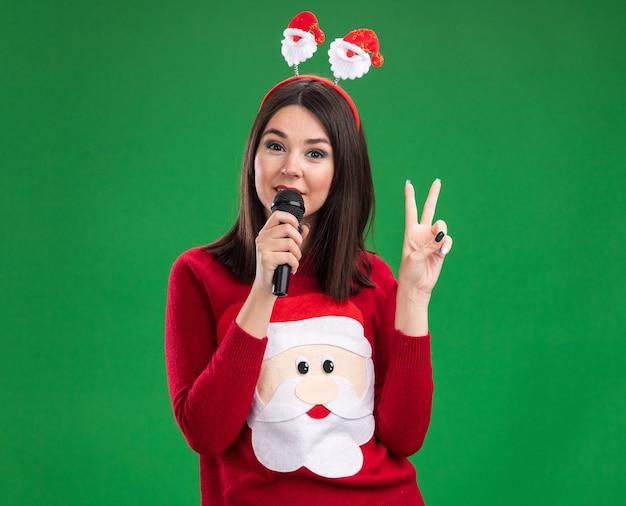 Уверенная молодая симпатичная кавказская девушка в свитере санта-клауса и повязке на голове разговаривает в микрофон, делая знак мира, изолированного на зеленой стене с копией пространства