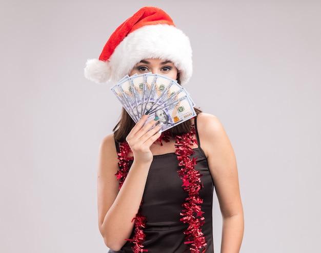 Уверенная молодая симпатичная кавказская девушка в шляпе санта-клауса и гирлянде из мишуры на шее держит деньги, глядя в камеру сзади, изолированную на белом фоне с копией пространства