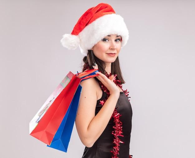 Уверенная молодая симпатичная кавказская девушка в шляпе санта-клауса и гирлянде из мишуры на шее, стоящая в профиль и держащая рождественские подарочные пакеты