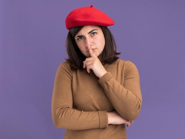 沈黙のジェスチャーをしているベレー帽の帽子を持つ自信を持って若いかなり白人の女の子