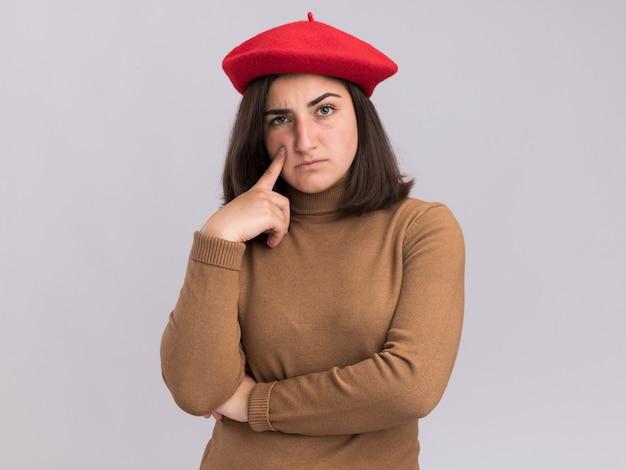 La giovane ragazza abbastanza caucasica sicura con il cappello del berretto mette il dito sul viso e guarda la telecamera