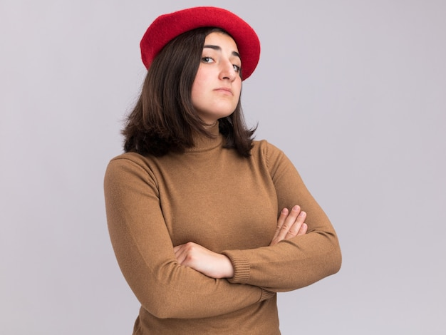 ベレー帽の帽子をかぶった自信を持って若いかなり白人の女の子は、腕を組んで立っています