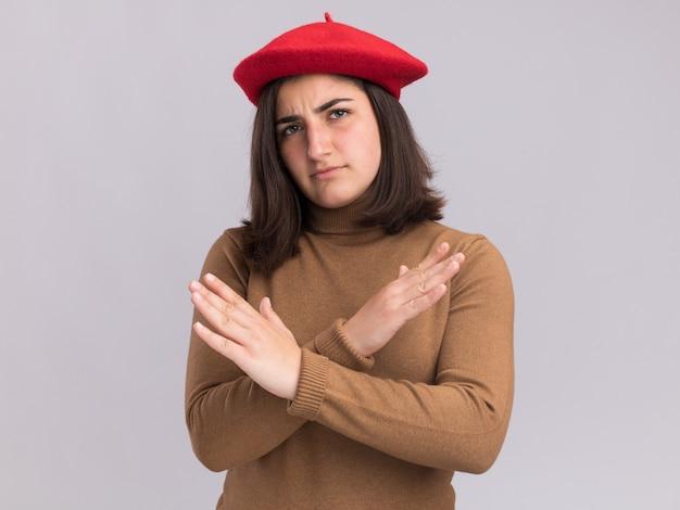 ベレー帽の帽子をかぶった自信を持って若いかなり白人の女の子は、兆候を身振りで示す交差した手で立っています