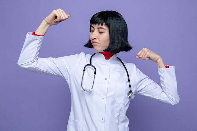 Fiducioso giovane bella donna caucasica in uniforme da medico con lo stetoscopio tende i bicipiti guardando a lato